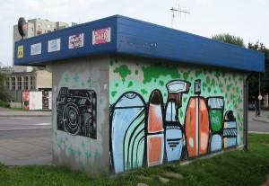 """Ul. Witosa. Drugi, bliźniaczy kiosk naprzeciw pierwszego. Ten jest czynny. Zwykły asortyment, jak to w kiosku. Jest też napis (z tej strony niewidoczny) """"Wspierajmy graffiti""""."""