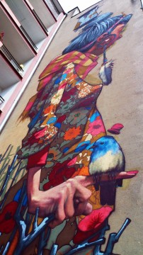 ul. Uniwersytecka 12, 2012, Sainer (Przemysław Blejzyk). Bodaj najsłynniejszy łódzki mural, do nabycia na koszulkach sprzedawanych przez Galerię Urban Forms. Praca dyplomowa na ASP.