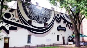 ul. Tuwima 16, 2013, M-City (Mariusz Waras). Chyba najlepszy moim zdaniem z całej kolekcji, wpisuje się w charakter miasta, wpasowuje w udostępnioną powierzchnię, jest też widowiskowy przez pewne iluzjonistyczne zabiegi artysty.