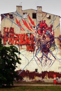 """ul. Wólczańska 109, 2012, """"Czas pożarł nas"""", Lump. Wielkie czerwone serce w pobliżu remizy strażackiej. Pod muralem na ławeczkach faktycznie przesiadują """"lumpy"""" z flaszkami. Nawet w południe, w dzień powszedni."""