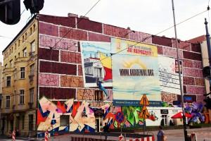 ul. Kościuszki, róg Żwirki, 2010, Tats Cru (Brooklyn, USA), Outline Colour Festival. Dwie pocztówki z widokami Łodzi, niestety przysłonięte reklamą. Chyba to robiła konkurencyjna organizacja, skoro mural nie jest włączony do GUF. Zresztą nie tylko on, jak się naocznie przekonałem.